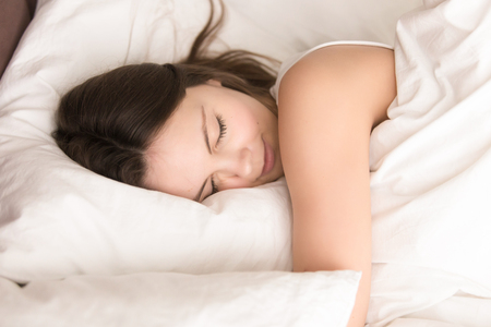 Young woman napping while hugging soft pillow, resting in cozy bed with fresh white sheets, smiling in her sleep. Healthy sleep, deep relaxing and strength renewal after hard work week concept