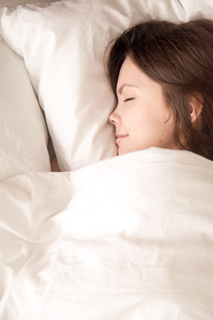 Young attractive woman sleeping in soft bed under warm blanket. Teenage girl falling asleep in bedroom after night party, seeing pleasant dreams in soft bed with fresh white sheets. View from above Stock Photo