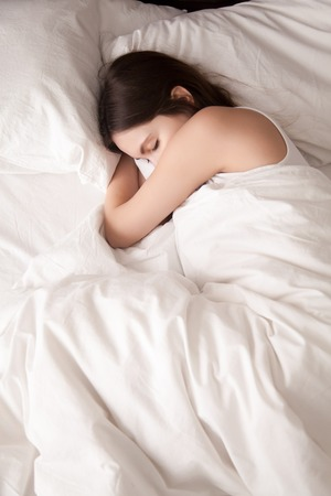 Tired young woman sleeping well on the side in bed with white sheets, resting after sleepless night. Female student lying in bed until late morning. Getting enough sleep concept. View from above
