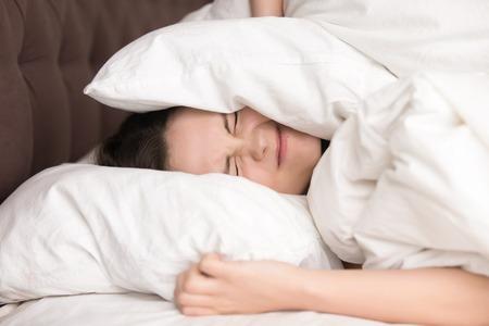 Vrouw liggend in bed bedekt hoofd met kussen, want te hard irritant geluid houdt haar de hele nacht lang. Geïritritiseerd vrouw dat lijdt aan luidruchtige buren, die probeert te slapen na het alarm wakker worden