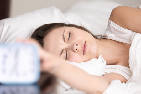 annoyed: Sleepy unhappy young woman turns off alarm clock signal while lying with eyes closed in bed at home. Frustrated female student hates to wake up and go to college. Hard morning awakening on early work