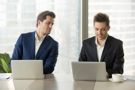 Curious businessman secretly looking at laptop screen of colleague, sneaking peek at other computer, stealing idea, copying private information on exam, nosy clerk spying on coworker at workplace Stock Photo