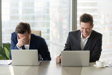 Deux hommes d'affaires éclaboussent de rire sur le lieu de travail, les employés de bureau hurlent de rire et ne peuvent pas arrêter, des émotions positives drôles au travail, des collègues enjoués s'amusant assis au bureau avec des ordinateurs portables