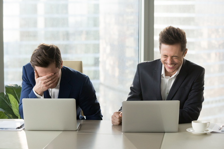 Two businessmen laughing out loud at workplace, office workers screaming with laughter and can not stop, funny positive emotions at work, cheerful colleagues having fun sitting at desk with laptops Imagens
