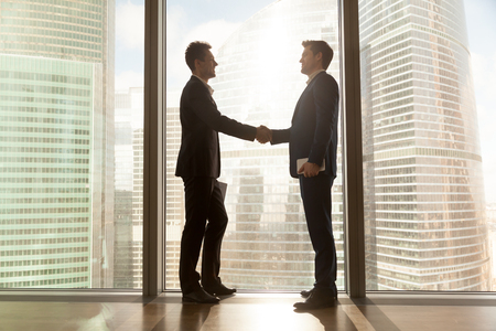 Two businessmen shaking hands standing at big window with urban cityscape, confident business partners handshaking in office, forming good relations, establish partnership, support, help. Side view