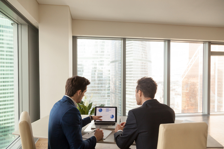 reviews: Two men discussing company growth, looking at rising graph on laptop screen, using easy accounting software for small business, stock traders analyzing market, pointing at charts on monitor. Rear view