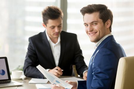 Sorridente uomo d'affari guardando fotocamera, analista finanziario o agente di borsa tenendo la carta con grafici e diagrammi, investitore felice successo analizzando mercato, analisi dei dati di business e servizi di consulenza Archivio Fotografico - 84037267