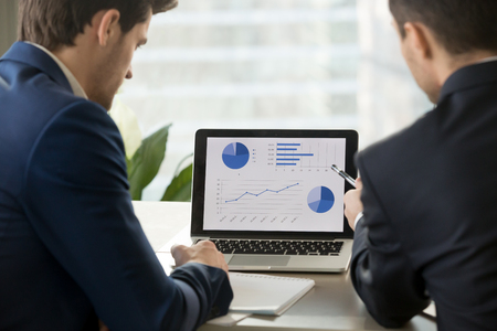 Rear view at two businessmen analyzing stats financial data on pc laptop, pointing at screen with rising graph and charts, discussing company growth, using easy accounting software for small business Stockfoto