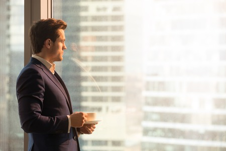 Side view of serious pensive director of prosperous company enjoying cup of coffee in the morning, thoughtful businessman in suit looking through big office window at dawn sunrise city, copy space