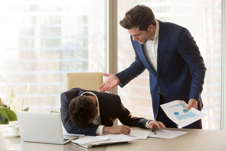 Bad angry boss yelling at male sad depressed employee, lying with face down on office desk, ineffective worker made mistake receiving reprimand from team leader, scolding for failure, missed deadline Фото со стока