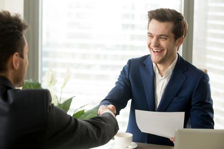 Gelukkig zakelijke partners handshaking na ondertekening wederzijds voordelige contract, zakenlieden dragen kostuums schudden handen over bureau, effectieve onderhandelingen, goede deal maken, partnerschap vormen Stockfoto