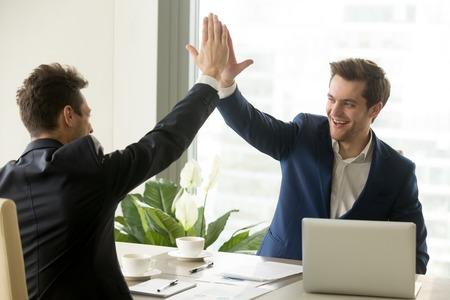 Uomo d'affari che dà il cinque alla sua compagna sulla riunione, squadra di gestione positiva che celebra la vittoria, affare di borsa di successo, crescita delle vendite, vinto buon contratto, successo aziendale e concetto di lavoro di squadra Archivio Fotografico - 83276198