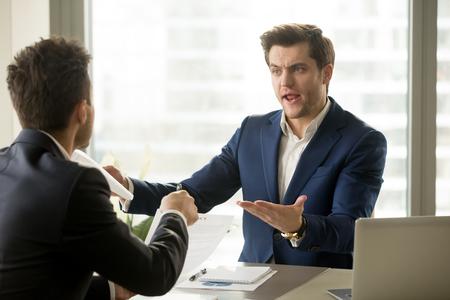 Uomini d'affari che discutono sul posto di lavoro, in disaccordo sul documento, partner che hanno conflitti durante la negoziazione, fallimento dell'affare, annullamento di accordi, rottura del contratto, termini inaccettabili