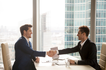 Two happy satisfied businessmen shaking hands over desk after successful negotiations, closing sealing deal, big window city building at background, smiling partners binding agreement with handshake Foto de archivo