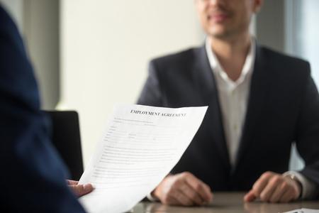 Solicitante con contrato de trabajo, considerando términos de trabajo, deberes de posición de lectura antes de firmar contrato laboral oficial, candidato a vacante exitoso contratado, colocación laboral, primer plano