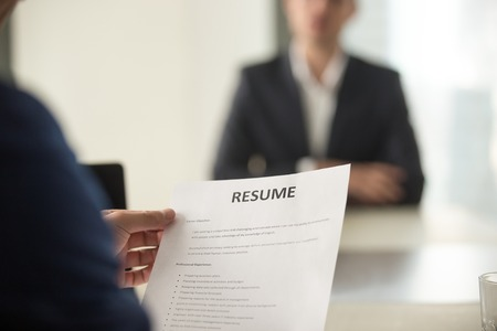 Close up view of job interview in office, focus on resume writing tips, employer reviewing good cv of prepared skilled applicant, recruiter considering application, hr manager making hiring decision Foto de archivo