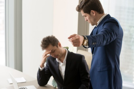 Angry boss dismissing frustrated upset male subordinate, dissatisfied employer telling employee to get out pointing with finger, fired from job, sad manager losing work and becoming jobless, laid off Stock Photo