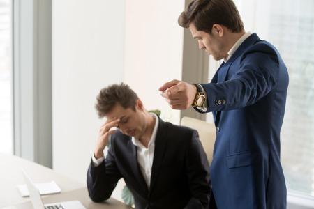 Boos baas ontslaan gefrustreerd overstuur mannelijke ondergeschikte, ontevreden werkgever vertellen werknemer om eruit te komen wijzen met de vinger, ontslagen uit baan, trieste manager werk verliezen en werkloos worden, ontslagen Stockfoto
