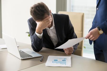 Droevige manager krijgt kennisgeving van ontslag, zit op de werkplek met laptop en financiële documenten, werknemer ontvangstbrief met slecht nieuws, ondernemer ontsteld door commercieel falen of stevig faillissement