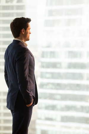 Serious confident businessman wearing blue suit standing in office looking at city buildings, lost in thoughts, enjoying sunset, waiting for meeting, making decision, vertical view, copy space Stock Photo