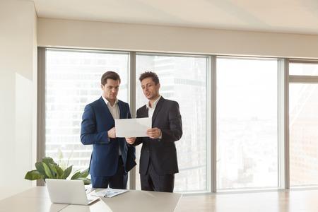 建物の計画、不動産を購入建設投資、合弁事業のパートナー、投資家に新しいプロジェクトを提供する投資顧問を議論する 2 つの深刻なビジネスマ 写真素材