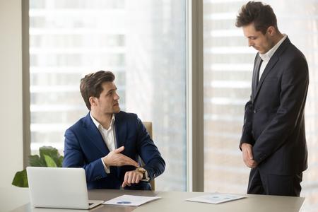Männlicher Untergebener, der vom Chef wegen zu spät am Treffen Rüge erhalten wird, Unternehmensleiter, der unpünktlichen Manager für fehlenden Stichtag schimpft oder Arbeit nicht rechtzeitig beendet, zeigend auf Armbanduhr