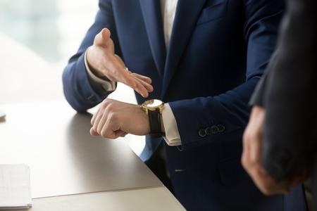 クローズ アップ会議、彼は遅刻示す守らなくパートナーで高価な高級腕時計を手で指しているスーツを着ているビジネスマンの表示時間厳守管理コ