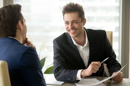 Twee glimlachende positieve zakenlieden die nieuw project bespreken op vergadering, het gekscheren en lachen, vriendschappelijke aardige manager raadplegende cliënt, partners die pret hebben tijdens bespreking, goede verhoudingen Stockfoto