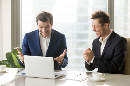 Two excited businessmen celebrating victory, won profitable contract, unexpected amazing win, big deal on stock, impressive achievement, unbelievable success, funny positive emotions at workplace Stock Photo