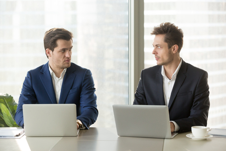 Two confident businessmen sitting at office desk with laptops, looking at each other with hate dislike, rivals accepting challenge, business competition, team rivalry at work, competitors behavior Stock Photo
