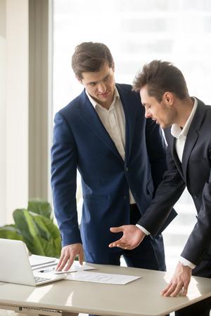 랩톱 및 건축 계획을 가진 건축 프로젝트에 종사하는 두 명의 감정인, 건설 투자를 고려하는 파트너, 상업용 부동산 구매, 구조화 된 디자인 토론, 수직