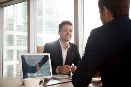 Smiling investment broker showing digital presentation on laptop screen to client, friendly salesman giving sales pitch, making business proposal to partner, selling product, offering cooperation