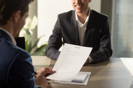 Vriendelijke werkgever uitvoeren sollicitatiegesprek, herziening van een goede CV van voorbereide bekwame lachende kandidaat te wachten op resultaat op de achtergrond, recruiter overweegt cv, focus op document, close-up weergave