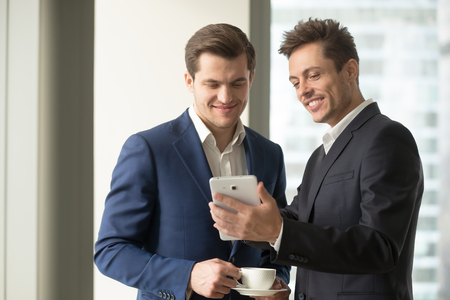 Smiling happy businessman holding digital tablet showing something funny interesting to colleague in office, discussing easy useful business applications or new trendy electronic gadget capabilities