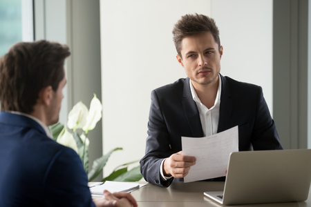Un hombre de negocios desconfiado que sostiene un documento en la reunión, mira a su compañero con sospecha de duda, el reclutador lee el currículum vitae malo, el solicitante atrapado es deshonesto en una entrevista de trabajo, trato turbio, fraude contractual