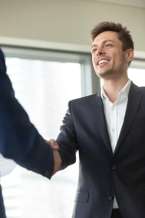 Glimlachende jonge zakenman die kostuum dragen die mannelijke hand schudden, die welkom het begroeten van handdruk op vergadering begroeten, aardig u te ontmoeten, goede eerste indruk, gelukkig om zich bij commercieel team aan te sluiten, die voor steun, verticaal bedanken Stockfoto