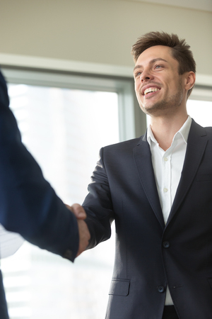 Smiling young businessman wearing suit shaking male hand, greeting welcoming handshake at meeting, nice to meet you, good first impression, happy to join business team, thanking for support, vertical Imagens