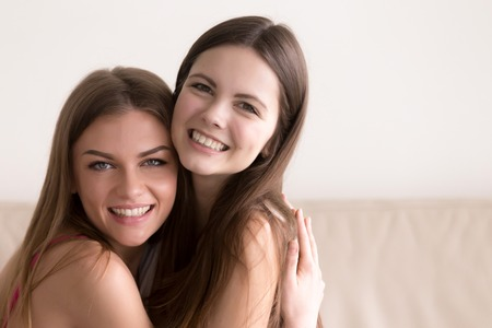 Close up headshot portrait of smiling young female friends warmly embracing during meeting. Two happy young women hugging and looking in camera. Strong friendship and sincere feelings between people