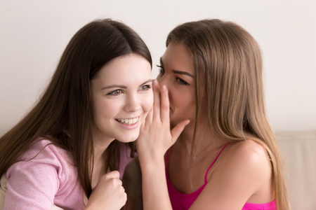 소년에 대해 험담 두 젊은 아름 다운 십 대 소녀의 얼굴 만 초상화. 자신의 비밀을 공유하고 귀찮은 뉴스를 전하고 귀에 관한 소문과 수다를 속삭이고  스톡 콘텐츠