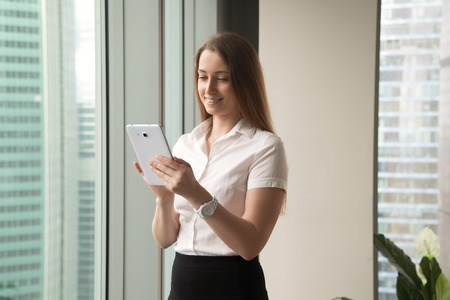 Attractive smiling businesswoman holding tablet pc standing near big office window, using business apps, enjoying internet banking, buying ordering online, making secure payment, browsing web service Stock Photo