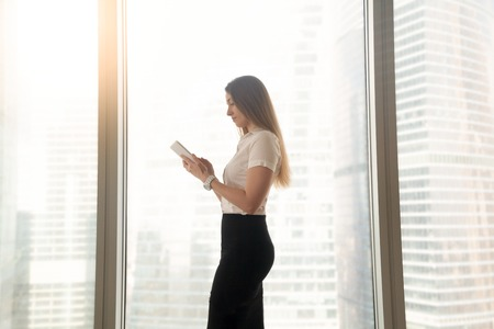 Busy serious businesswoman using digital tablet computer business apps in office, female manager focused on planning work on corporate mobile device, internet banking, communicating online, side view Stock Photo
