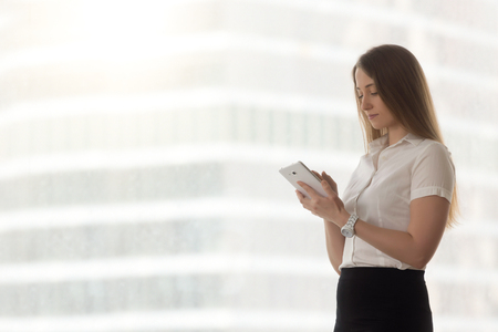 Confident successful businesswoman holding digital tablet, female small business owner stays in touch communicating with customers by handy device, company executive using business apps, copy space