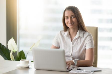 Donna di affari attraente che lavora al computer portatile e che sorride per la macchina fotografica in posto di lavoro, riuscito direttore esecutivo sicuro che si siede alla scrivania, giovane proprietario di e-business che posa sul lavoro, ritratto di colpo in testa Archivio Fotografico - 86667362
