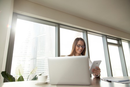 Smiling confident businesswoman using tablet computer sitting at workplace, working with corporate devices at office desk, planning work with apps, banking online, mobile digital business management