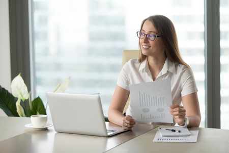 Smiling businesswoman satisfied with fast growing startup, holding financial report with rising statistics, upward charts, increased sales, dreaming of future company prosperity and business success
