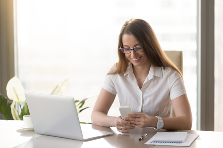 Beautiful smiling business lady using smartphone while sitting at desk, happy businesswoman holding new white cellphone, reading or texting message, dialing number to contact client, mobile banking Фото со стока