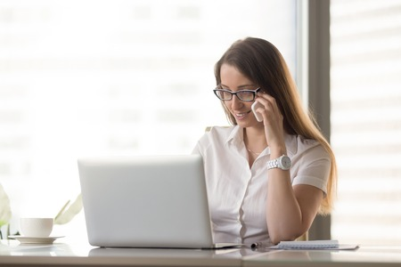 Smiling businesswoman talking on phone while using laptop at workplace, manager calling client to make appointment, arranging meeting by telephone conversation, consulting customer about online order Stock Photo