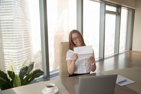 Mulher de negócios feliz que guarda o original de negócio e que sorri ao sentar-se na mesa de escritório perto do portátil, lendo a boa notícia na letra da aprovaçã0, apreciando a notificação escrita agradável do correio da descarga Foto de archivo - 86667371
