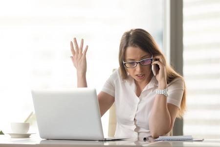 Empresaria enojada descontenta que discute sobre la sesión móvil en el lugar de trabajo, tiene problemas de conflicto durante las negociaciones telefónicas, no está de acuerdo por celular, grita y gesticula mientras habla en un teléfono inteligente
