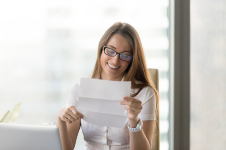 Portrait of smiling businesswoman in glasses reading positive business letter, holding document with good news while sitting at home office desk, feeling happy by loan approval notification, got job